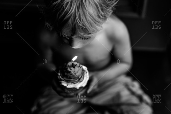 Boy blowing out a candle on a birthday cupcake