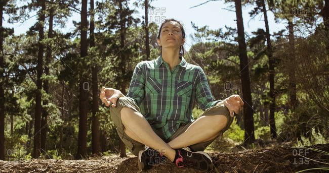 Woman is doing yoga in the wood on a sunny day