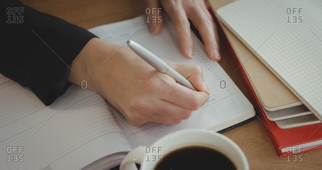 Close up of businesswoman is writing on a notebook at the office