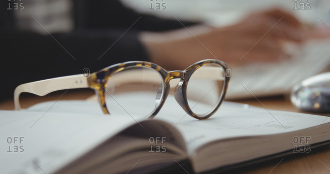 Close up of glasses is putting on a book on a desk