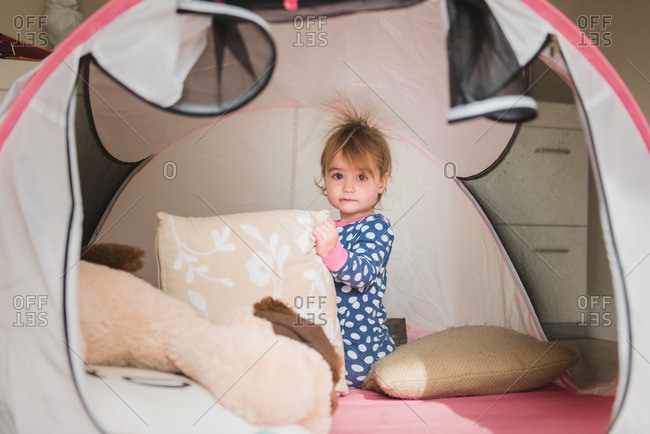 Toddler girl in play tent with hair standing up from static electricity