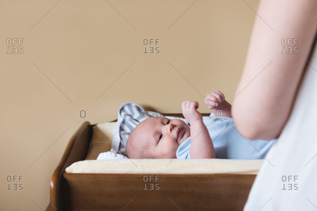 Mother changing newborn baby on changing table