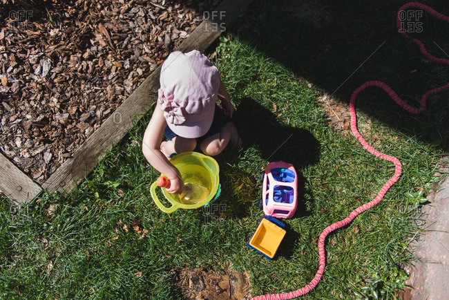 Overhead view of toddler playing with pail and shovel in garden