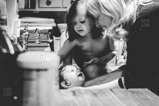 Young baby smiles while being bathed in sink by grandmother and sister