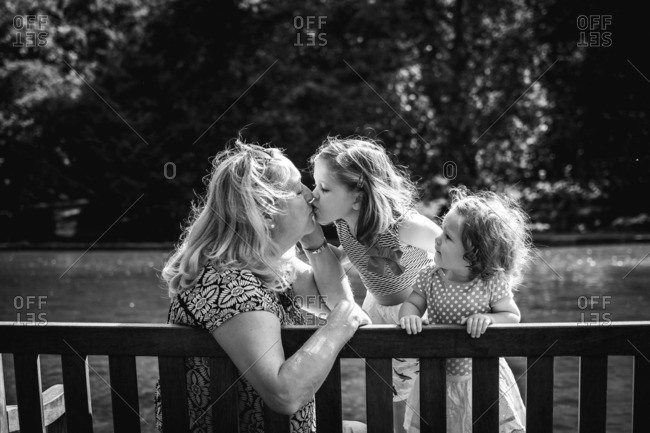 Toddler girl kisses her grandmother as her young sibling watches