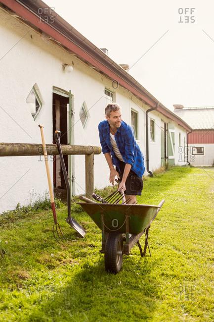 Smiling farmer removing equipment from wheelbarrow at farm