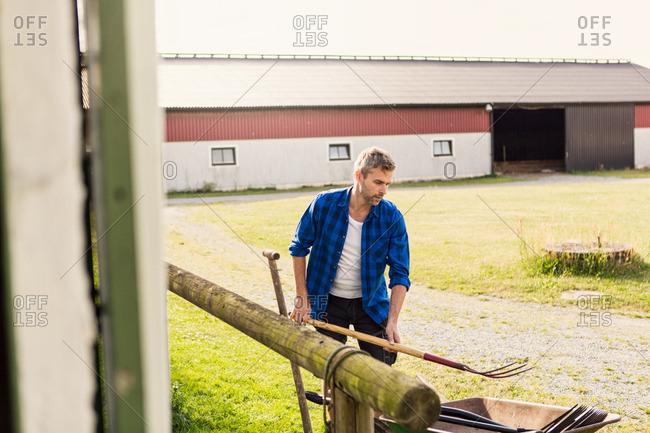 Farmer arranging equipment outside barn at farm