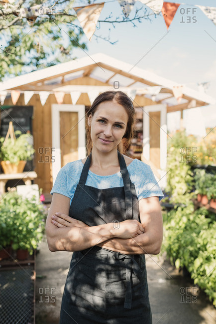 Portrait of confident female owner standing in garden against food store
