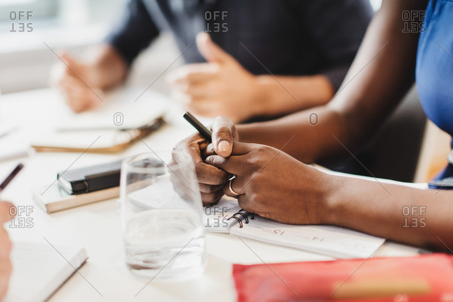 Close up of a woman's hand on her notebook at table