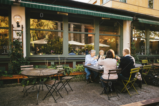 Happy senior couples toasting champagne flutes at outdoor restaurant