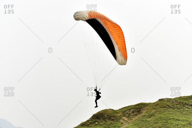 Man paragliding in silhouette