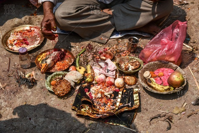 Man by Hindu offerings