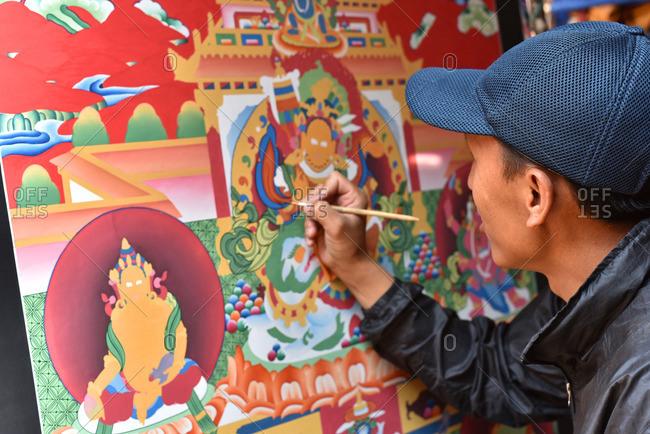 Nepal - April 15, 2016: Nepali man painting religious scene