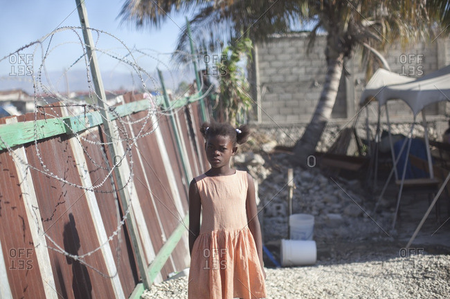 Haiti - February 20, 2011: Girl standing outside in orange dress