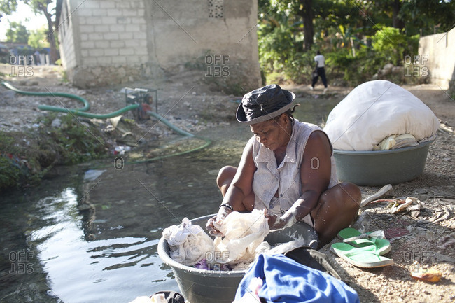 Haiti - February 23, 2011: Woman washing clothes in a river