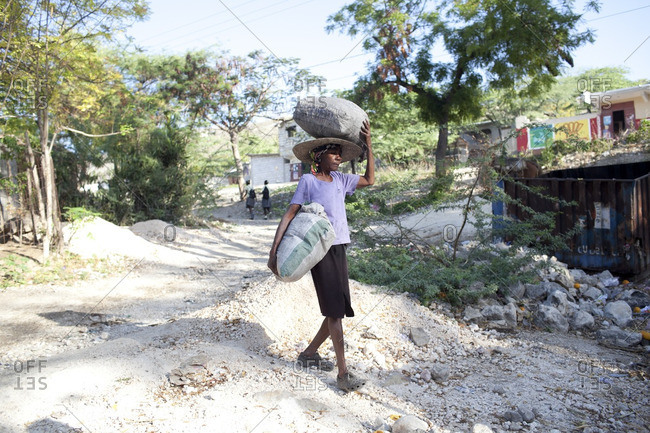 Haiti - February 23, 2011: Woman carrying burlap sacks