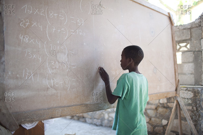 Haiti - February 24, 2011: Haitian boy doing math on a classroom chalkboard