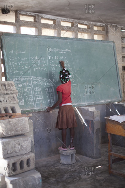 Haitian girl doing math on a classroom chalkboard