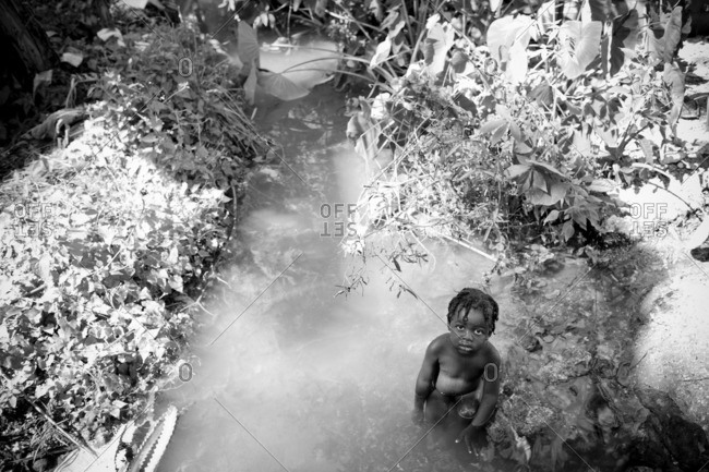 Haiti - February 25, 2011: Small Haitian boy bathing in a river