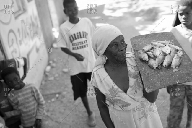 Haiti - February 25, 2011: Woman carrying fish on a tray