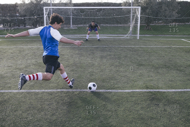 Soccer player kicking a ball in front of a goal with a goalkeeper