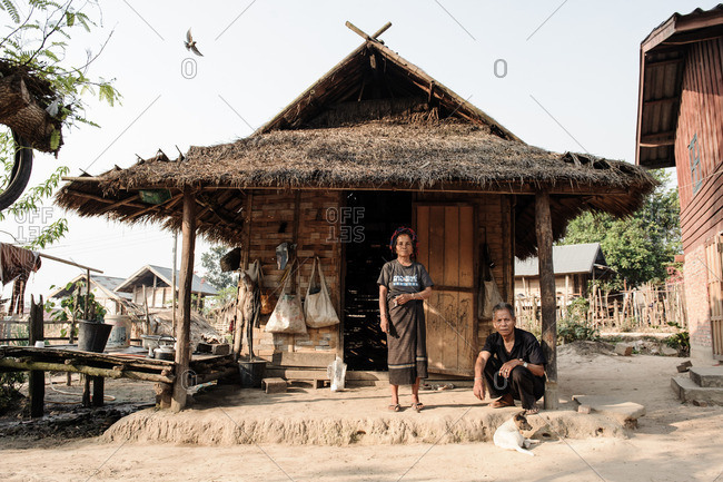 Laos, Asia - December 26, 2015: Villagers on the porch of their hut in Laos