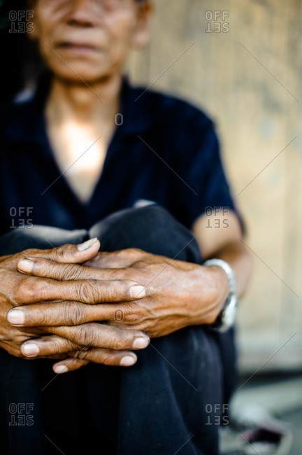 Laos, Asia - December 26, 2015: Close up of a Laotian woman sitting with hands together