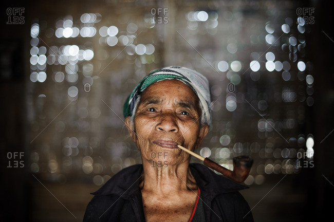 Laos, Asia - December 26, 2015: Portrait of a Laotian woman smoking a pipe