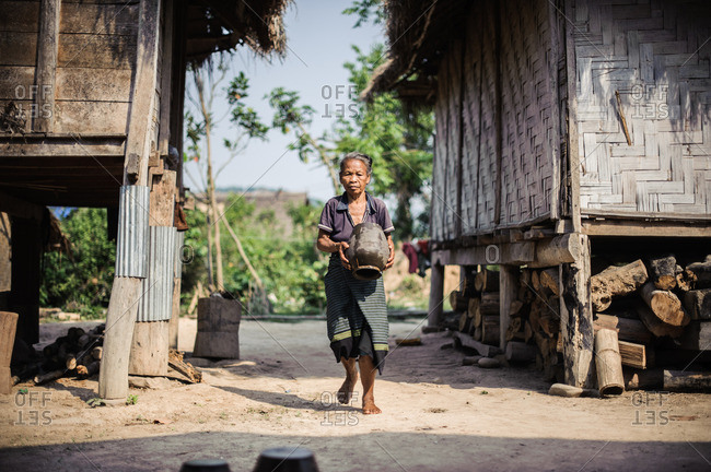 Laos, Asia - December 26, 2015: Woman carrying vase through village in Laos