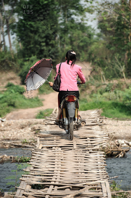 Laos, Asia - December 26, 2015: Woman riding motorbike over bridge in Laos