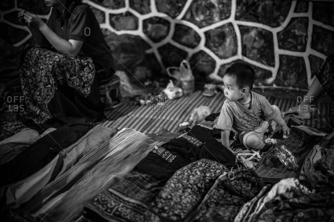 Luang Prabang, Laos, Asia - April 28, 2012: Baby sitting among fabrics at a market in Luang Prabang, Laos