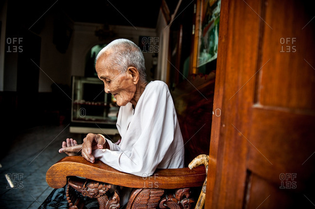 Luang Prabang, Laos, Asia - April 29, 2012: Elderly Laotion woman sitting on a wooden bench