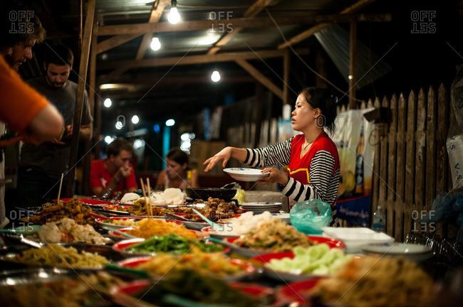 Luang Prabang, Laos, Asia - April 28, 2012: Woman selling food at a market in Luang Prabang, Laos
