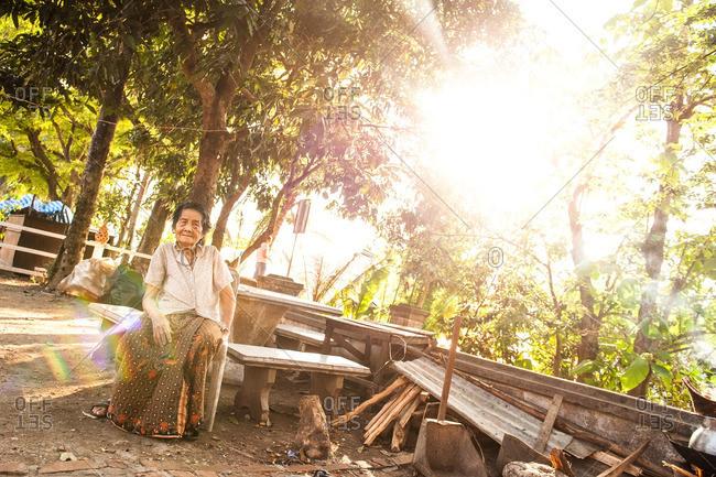 Luang Prabang, Laos, Asia - April 29, 2012: Old woman sitting on an outdoor bench in Luang Prabang, Laos