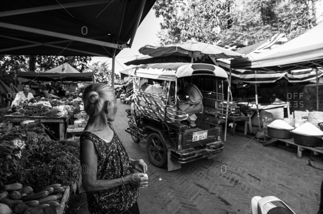 Luang Prabang, Laos, Asia - April 29, 2012: Woman watching tuk tuk pass in the street in Luang Prabang, Laos