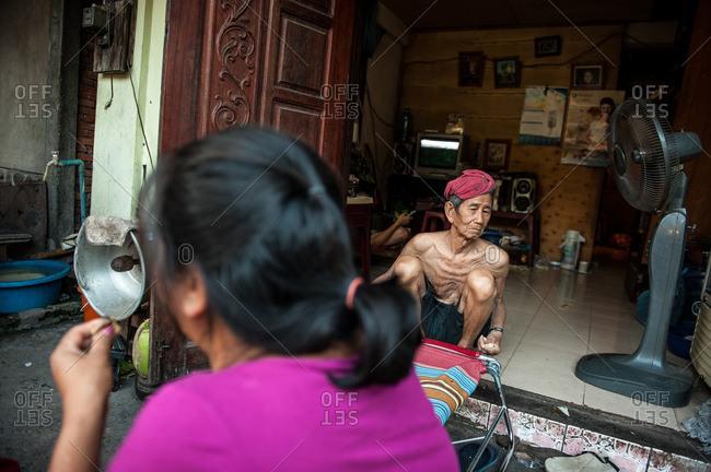 Luang Prabang, Laos, Asia - April 29, 2012: Old man sitting in open doorway to his residence in Luang Prabang, Laos