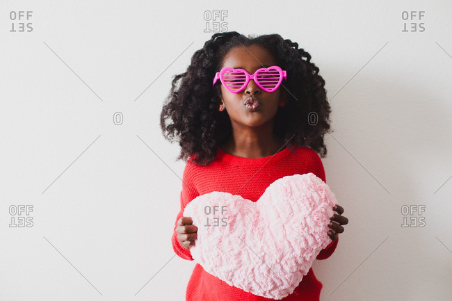 Girl in sunglasses with heart pillow
