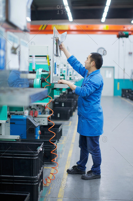 Worker at small parts manufacturing factory in China reaching up to press button on control panel