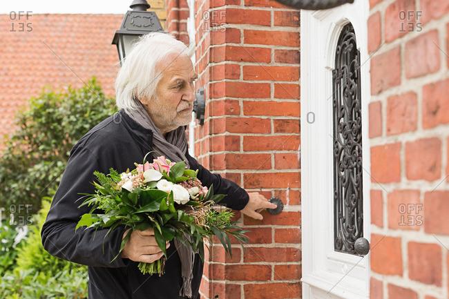 Senior man with bouquet ringing doorbell
