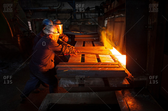 100mm square steel billet is removed from furnace as cold steel billet waits in foreground to be heated