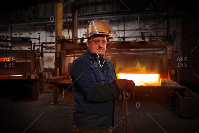 """Forge worker, second in command of hammer control or """"stamper"""" in pre forming forging area with a set of industrial tongs as furnace door is closed"""