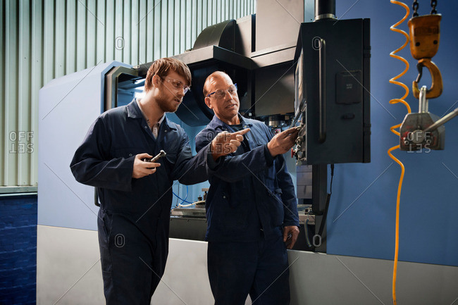 An experienced worker explains the workings of a CNC machine to an apprentice