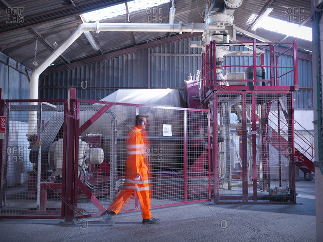 Worker in reflective clothing passing machinery in zircon flour mill