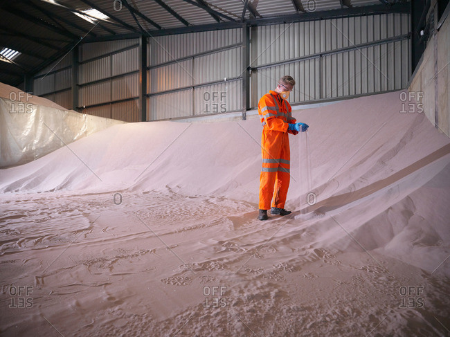 Worker in reflective clothing inspecting zircon sand