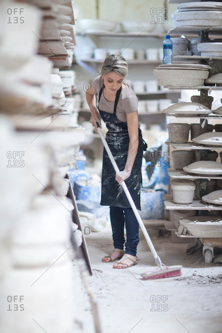 Potter sweeping floor at crockery factory