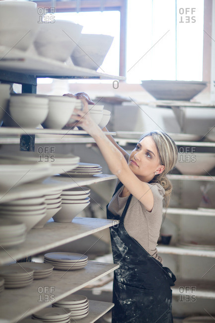 Potter stacking bowls onto shelf at crockery factory