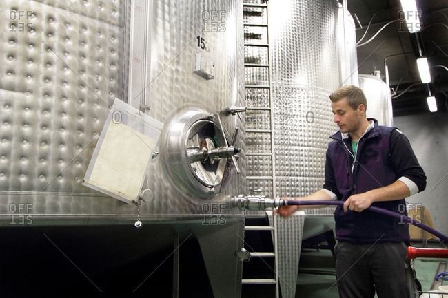 Man working in industrial wine cellar