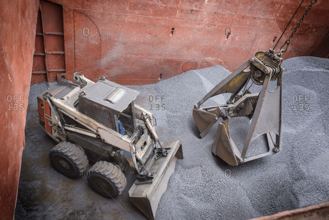 High angle view of digger and grab unloading metal alloy in ship's hull