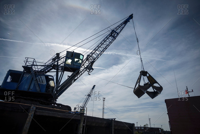 Low angle view of crane in silhouette in port