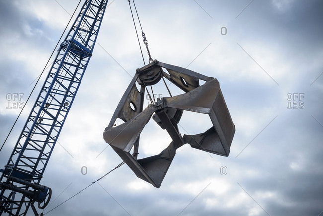Low angle view of crane grab against cloudy sky